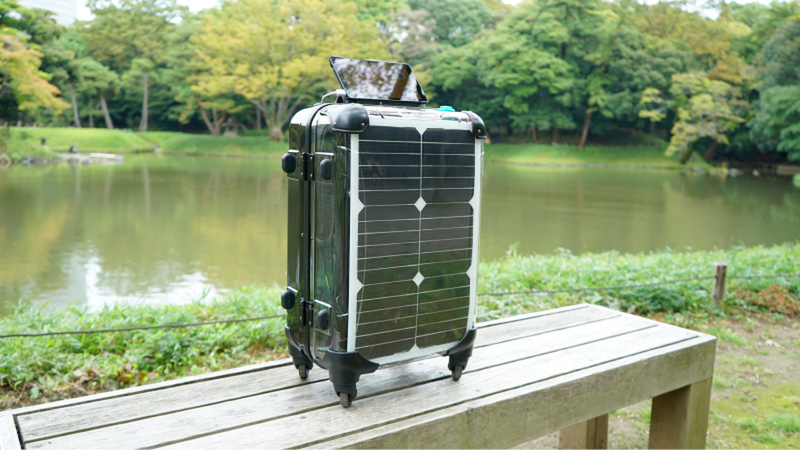 A medium-sized luggage with solar panels on the sides stands on a bench in front of a lake at a park.