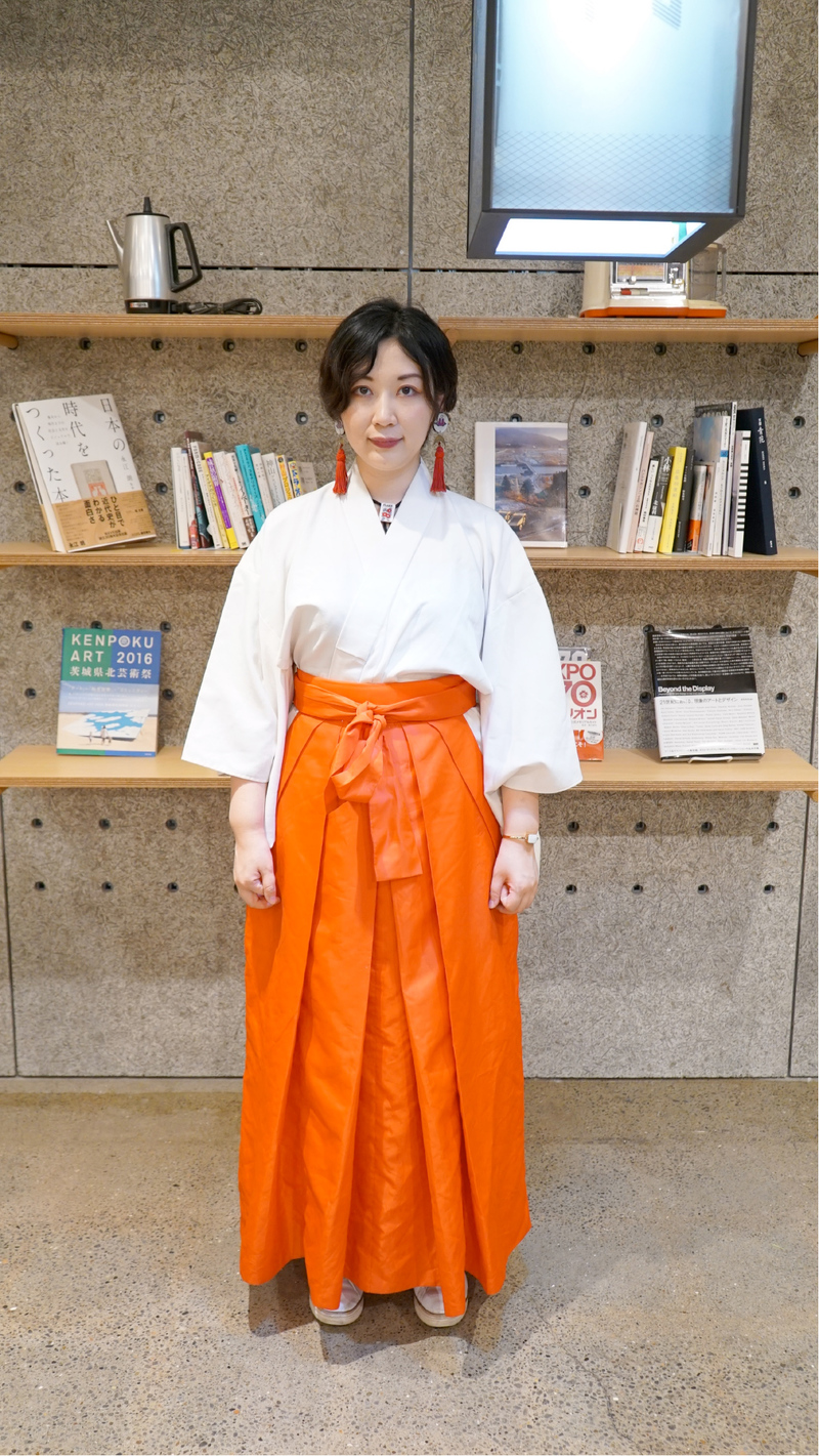 Etsuko Ichihara stands in front of three bookshelves wearing a white shirt and orange kimono-like skirt