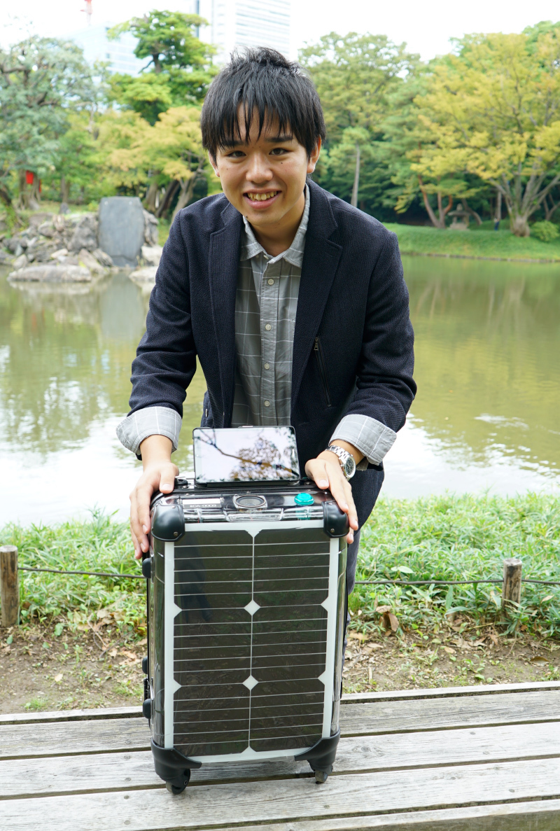 Kazumi Muraki stands with a smile behind a medium-sized luggage with solar panels on the sides stands on a bench in front of a lake at a park.