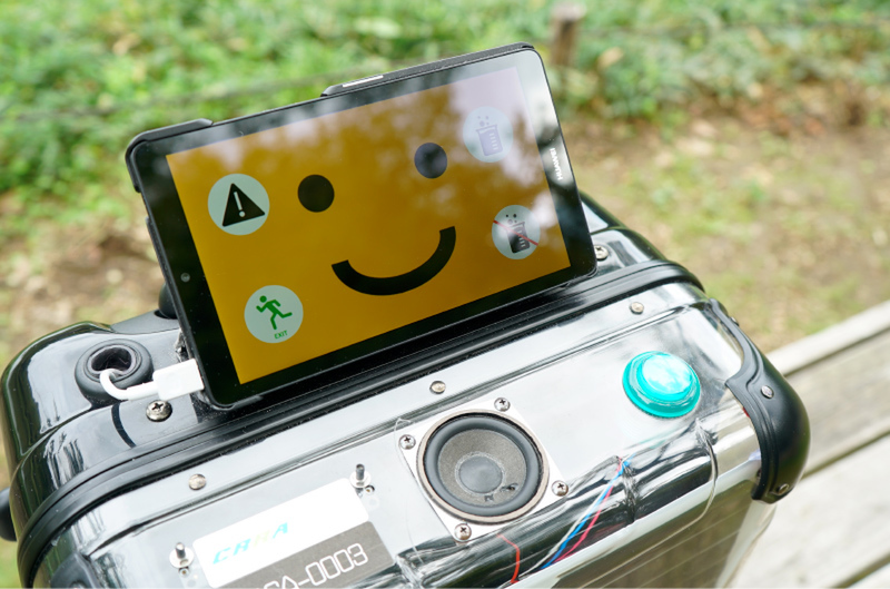 A medium-sized luggage with solar panels on the sides and a tablet with a orange smiley face on top stands on a bench in a park.