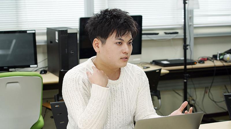 Takayuki Kameoka sitting down in front of a laptop wearing a white shirt.