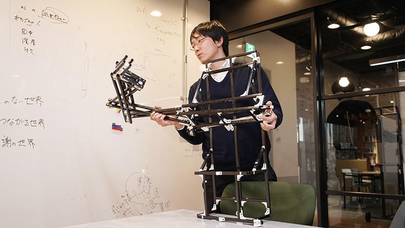 Kazutoshi Tanaka grabs a robotic frame made of thin black metal bars.