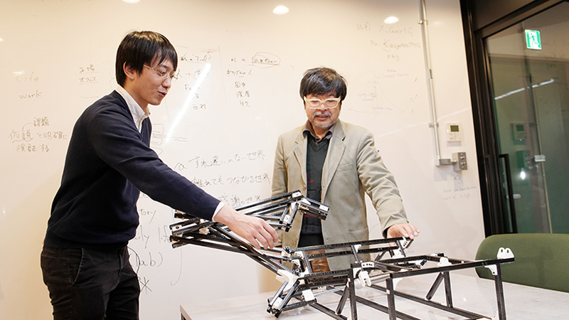 Kazutoshi Tanaka demonstrates the robotic frame's movement to the interviewer, Satoshi Endo