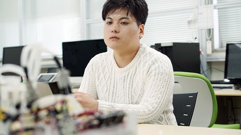 Takayuki Kameoka sits wearing a white shirt.