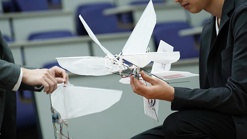 A man holds a white lightweight robot that has the shape of a dragonfly