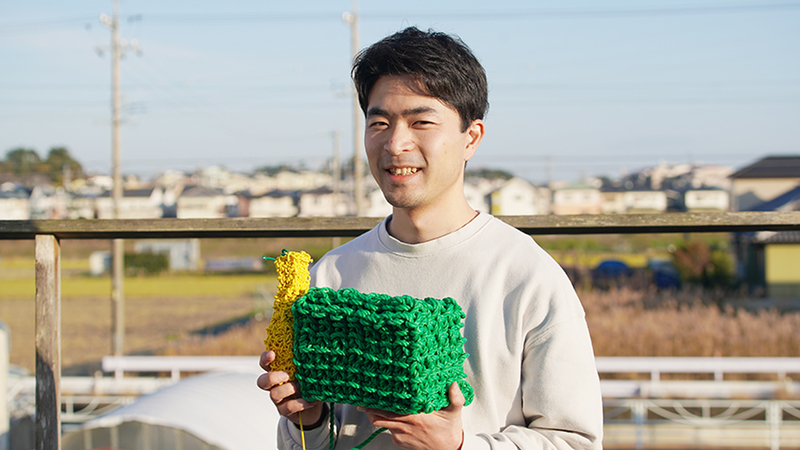 Hirose Yuichi standing outside holding two of his solid knitting creations.