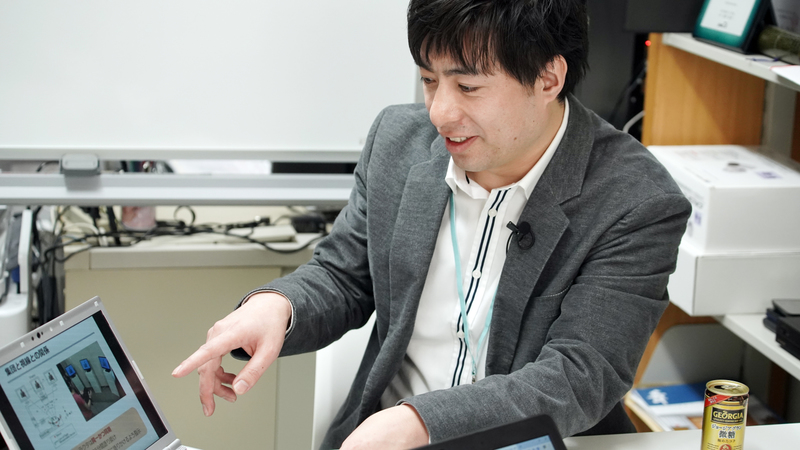 Yoshihiro Sejima sits at a desk and points to a laptop screen.