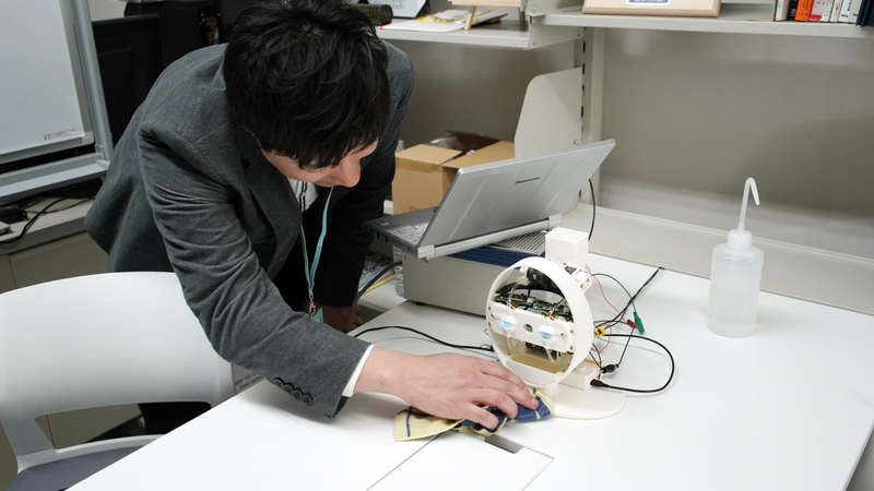 Yoshihiro Sejima uses a cloth to clean the base of the robot with eyes