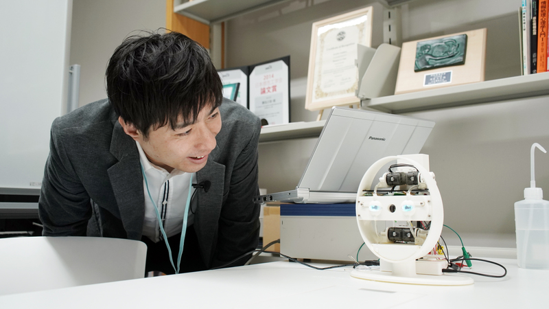 Yoshihiro Sejima leans over and looks at a small circular robotic device with human-like eyes.