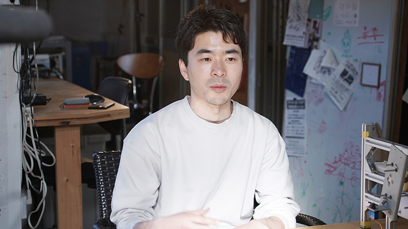 Hirose Yuichi sitting down and wearing a white shirt.
